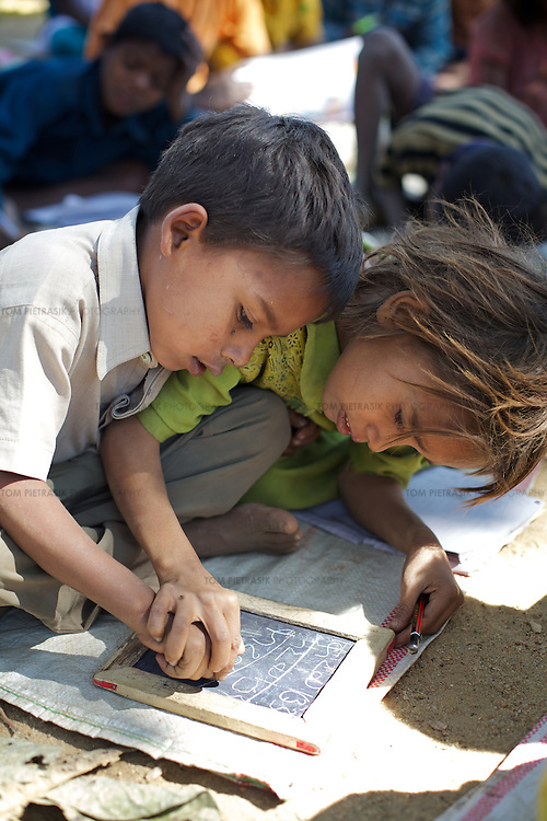 Students at the Jalhe Bogiya village school where they now enjoy a hot lunch six days a week thanks to the midday meals program. <br /> <br /> Lack of irrigation and food security lie at the root of the Maha Dalit community's problems in the village of Jalhe Bogiya. In the exploitative and divisive caste system, Maha Dalits are considered the lowest of the low. Ostracized by wider society (including the administration) illiteracy runs as high as 95 percent. Thanks to Oxfam-supported intervention, Jalhe Bogiya now has an - as yet incomplete - access-road built as part of the NREGA (National Rural Employment Guarantee Scheme). And an Oxfam-supported initiative in summer 2010 successfully lobbied the local administration to implement the provision of school midday meals which, by law is the right of every child. It is alleged that the Anganwadi (pre-school) centre administrator, syphons off food meant for young children. Jalhe Bogiya has several hand pumps supplying water but these do not work between the months of May to October. And though the village was connected to the electricity grid six months ago, power-supply is not reliable. Without land-ownership and only irregular agricultural work from which to earn an income, the Maha Dalits of Jalhe Bogiya frequently migrate in search of labour at stone breaking quarries, brick-kilns or undertake menial household work in the homes of the urban middle class in far-away cities. <br /> <br /> Photo: Tom Pietrasik<br /> Mohanpur Block, Gaya District, Bihar. India<br /> February 23rd 2011