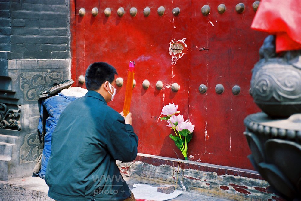 China, Taiyuan, 2008. Taiyuan's main Buddhist temple closed down during the three months of China's SARS outbreak in 2003. The devoted still came, praying outside while wearing masks.