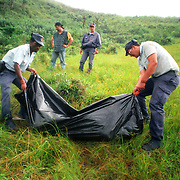South African police recover the body of a villager near the hamlet of Shoboshobane, on the KwaZulu/Natal South Coast.  On Christmas Day, the ANC village was attacked by Inkatha neighbours killing more than 20 residents, and drriving the rest into refugee camps.  December 26th, 1995.