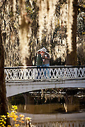 A couple kisses on the bridge at Magnolia Plantation Charleston, SC