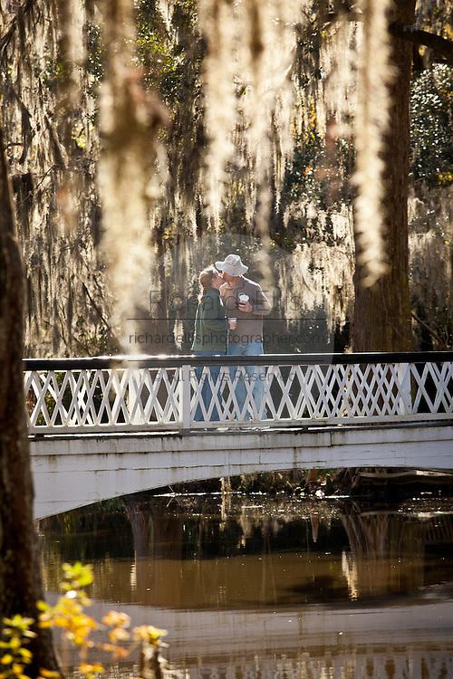 A couple kisses on the bridge at Magnolia Plantation Charleston, SC
