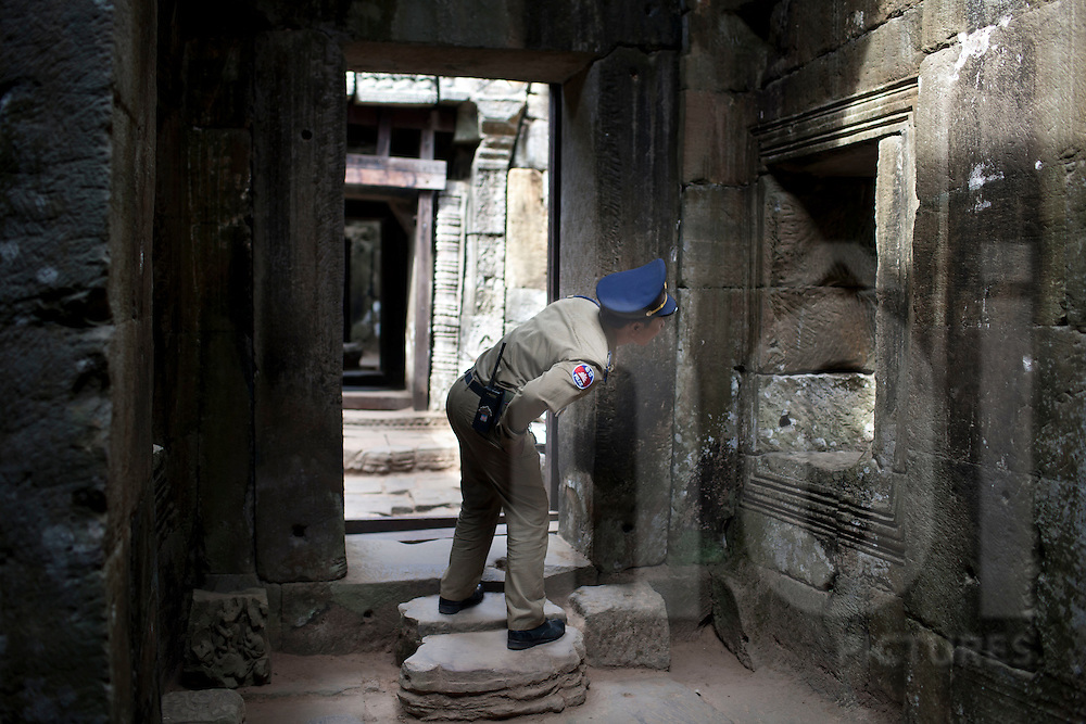 An officer inspects and monitors the areas within the old Angkor ruins, Cambodia, Southeast Asia