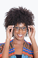 Portrait of young woman in African print attire wearing glasses over gray background