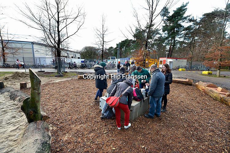 Nederland, the Netherlands, Nijmegen, 25-11-2015Vluchtelingen houden zich op, wandelen, bij kamp, tentenkamp Heumensoord, de tijdelijke noodopvang, azc, van het COA. Een vrijwilligster heeft enkele kannen koffie meegenomen waar tegenover de toegang naar het kamp dankbaar gebruik van wordt gemaakt. FOTO: FLIP FRANSSEN