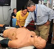 Pre-med student, Katherine Banares, (left), receives instruction from Dr. Allan J. Hamilton at the Arizona Simulation Technology and Education Center, University Medical Center, University of Arizona, Tucson, Arizona, USA.