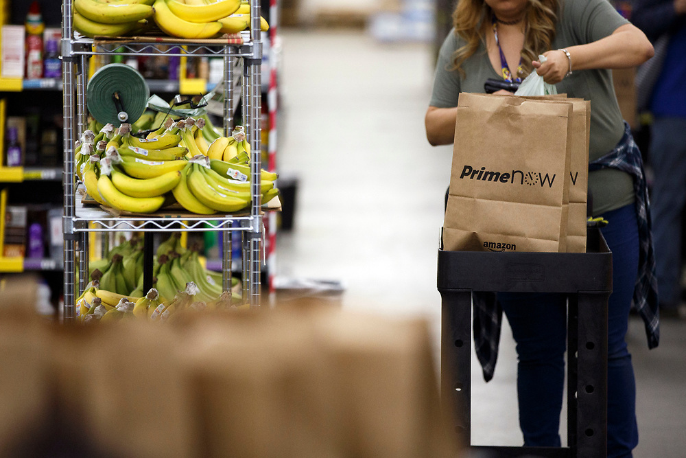 An Amazon associate bags bananas at the Amazon.com Inc. Prime Now fulfillment center warehouse on Monday, March 27, 2017 in Los Angeles, Calif. The warehouse can fulfill one and two hour delivery to customers. Complex supply chains such as Amazon's and e-commerce trends will impact city infrastructure and how things move through cities. © 2017 Patrick T. Fallon