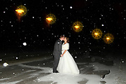 Bride and groom kissing at night in falling snow along a road with street lamps, White Eagle, Hamilton, NY