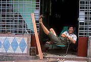 Man relaxing in a chair in the doorway to his shop. Rangoon, Burma 2001