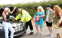 © Licensed to London News Pictures. 25/06/2014. PILTON, UK. Dolly Parton lookalike spotted singing to broken down motorist. Arrivals at Glastonbury Festival today 25th June 2014. Glastonbury Festival 2014 takes place between Wednesday June 25 and Sunday June 29, 2014. Photo credit : Jason Bryant/LNP