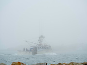 A lone lobster boat returns to port at Cape Forchu, Nova Scotia, Canada.