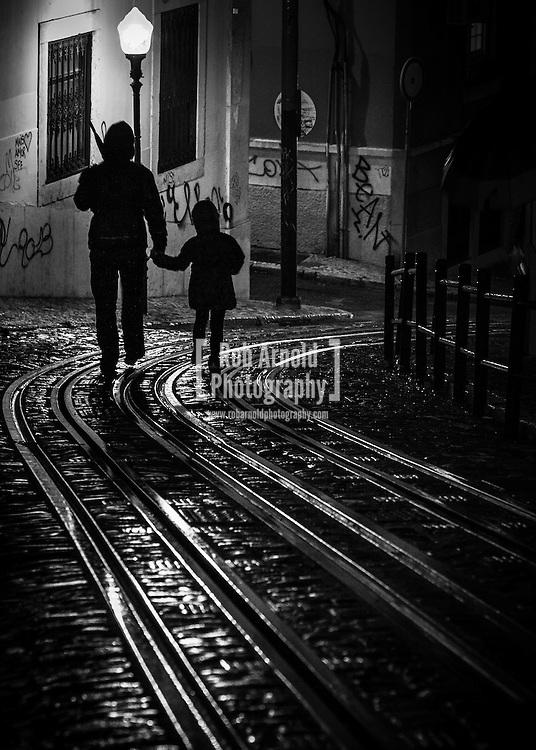 A man and boy walking through a dark, damp side-street in the Portuguese capital of Lisbon