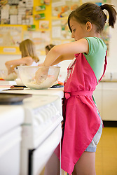 Profile of a young girl in cookery class kneading