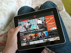 Man reading digital app edition of CNN news on an iPad touch screen tablet computer
