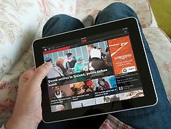 Man reading digital app edition of CNN news on an iPad touch screen tablet computer