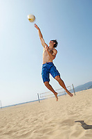 Young man jumping hitting volleyball on beach