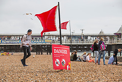 © Licensed to London News Pictures. 11/06/2017. Brighton, UK. Danger signs and red flags are visible all over the beach in Brighton and Hove to warn the public of the powerful waves. Photo credit: Hugo Michiels/LNP