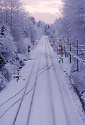 Fresh snow on rail road tracks leading off