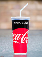 London, England - July 23, 2017: Cup of Coca Cola with Straw, Coca-Cola  was first introduced in 1886 in the USA.
