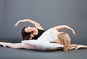 Two young female ballet dancers doing the splits over grey background