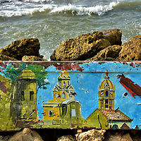Painting of City Landmarks in Bocagrande, Cartagena, Colombia <br /> The rusted metal box wedged into the seawall of the Bocagrande beach seemed like an odd canvas for a painting.  However, the colorful images are immediately recognizable as the city's landmarks. They are, from left to right, a sentry tower on the defensive wall, the Torre de Reloj or Clock Tower, and the Cathedral Cartagena's belfry.