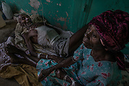 RENDEL, HAITI - OCTOBER 12, 2016:  Faniel Cyril, (left) and his cousin, Alicia Delcy (center) who are both suffering symptoms of Cholera contracted in Delibarain, the small village where they live, and where many believe this outbreak originated. Frightened of what was happening in their village, the pair had come down the mountain on Sunday to seek treatment. Faniel, barely conscious, reached out to grab the hand of Mrs. Delcy from time to time.