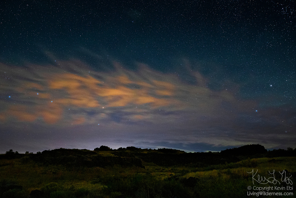 A band of altocumulus clouds, partially illuminated by city lights, pass over rugged cliffs that are remnants of ancient lava flows in Columbia National Wildlife Refuge near Othello, Washington.