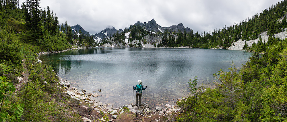 Kaleetan Peak (left 6259 ft / 1908 m) rises into cloud above Gem Lake in Alpine Lakes Wilderness Area in the Cascade Range of Washington, USA. In mid July, we hiked to Gem Lake 10 miles round trip with 2800 feet cumulative gain along Snow Lake Trail #1013 in Mt. Baker-Snoqualmie National Forest. Take Interstate 90 Exit #52 westbound or Exit #53 eastbound and follow signs to Alpental Road ski area parking lot and trailhead. To avoid crowds at this popular trail, start early and avoid sunny weekends. The trail down from the saddle viewpoint to Snow Lake is often snow covered through July 4. This image was stitched from 11 overlapping photos.