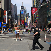 The Naked Cowboy performing in Time Square, New York, as Police Officers walk past. Times Square is the major commercial intersection in Midtown Manhattan, New York City. Time Square, New York, USA. 27th April 2012. Photo Tim Clayton