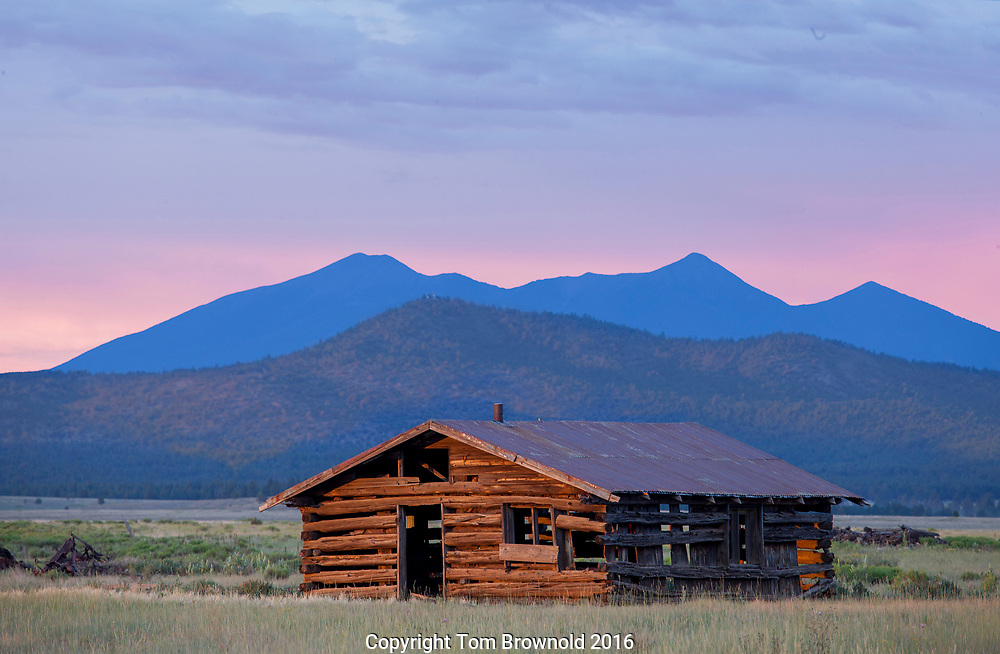 The San Francsico peaks and an old decaying log cabin in Garland Prairie at twilight