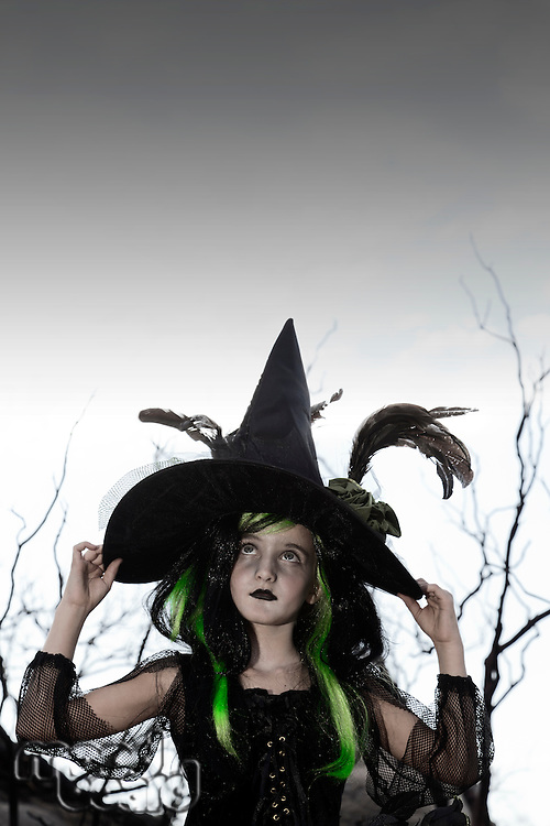 Girl costumed as witch looking up holding her hat