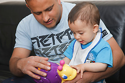 Father and son at home playing with toy.