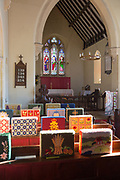Knitted woollen pew kneelers rest on wooden pews, view towards altar and stained glass east window, interior of church at Stert, Wiltshire, England, UK