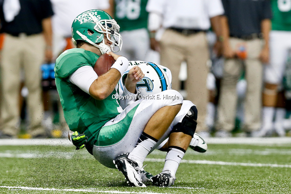 Oct 5, 2013; New Orleans, LA, USA; Tulane Green Wave cornerback Jordan Batiste (14) tackles North Texas Mean Green quarterback Derek Thompson (7) during the first half at Mercedes-Benz Superdome. Mandatory Credit: Derick E. Hingle-USA TODAY Sports