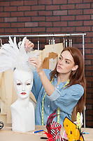 Female fashion designer adjusting feather fascinator on mannequin