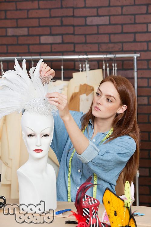 Female fashion designer adjusting feather fascinator on mannequin