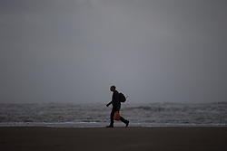 "© Licensed to London News Pictures . 10/12/2014 . Blackpool , UK . A lone man walks along the beach . An explosive cyclogenesis - a fast developing storm in which air pressure falls rapidly - known as a "" weather bomb "" - hits the North of England , bringing storms to the region . Photo credit : Joel Goodman/LNP"