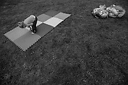 """A child inspects pieces of an indoor play mat in the Union Springs neighborhood during the annual """"50 Mile Yardsale"""", Saturday, July 20, 2016 along Route 90 in the Cayuga Lake region of the Finger Lakes, New York."""