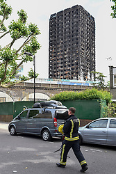 © Licensed to London News Pictures. 23/06/2017. London, UK. A firefighter en route to the inspection zone.  Nine days on, police have reported that the Grenfell Tower fire in west London started in a fridge-freezer, and outside cladding and insulation failed safety tests. Photo credit : Stephen Chung/LNP