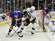 New York Islanders' Jesse Joensuu (58) and  Penguins' Chris Kunitz (14) battle for the puck as Penguins goalie Marc-Andre Fleury (29) and Islanders'  Matt Martin (17) look on during an NHL hockey game Friday, April 8, 2011, in Uniondale, N.Y. (AP Photo/Kathy Kmonicek)
