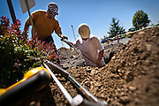 Roger Sahli, left, takes a handful of wiring for new parking lot lighting from Matt Jacobs, right, outside the Kootenai County Sheriff's Office on Government Way. The new building is designed to make the building more handicap accessible and comply with the Americans with Disabilities Act standards for building construction.