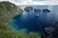 The ship Shakti, chartered for the GEO Expedition, is tied off in small bay surrounded by limestone cliffs and islets..Misool Island vicinity.  Near smaller island of Fiabacet.