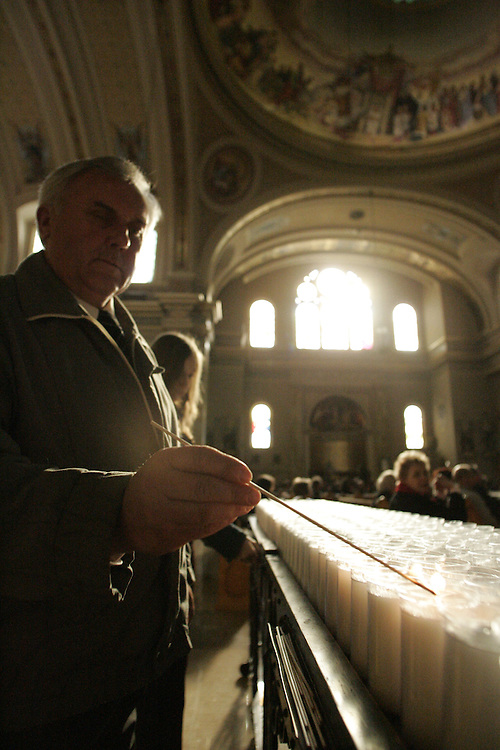 Wally Kaminski lights candles just before mass at St. Hyacinth Basilica, a Polish Catholic church in Chicago after the death of Pope John Paul II...