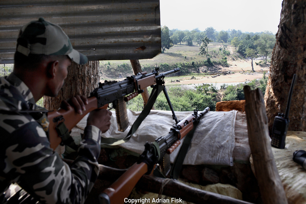 In the police post at the Salwa Judam camp in Errabore a policeman watches carefully over the landscape for a possible Naxalite attack. Previously the camp was attacked resulting in the deaths of 55 police and Salwa Judam Militia members.