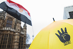 London, UK. 25 January, 2020. The R4bia hand sign appears on an umbrella at a protest outside Parliament against the Egyptian government of President Abdel Fattah el-Sisi by supporters of the Egyptian Revolutionary Council and UK anti-Coup organisations.
