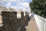 A couple, a man and a woman, walk along the historic city walls in York, UK.