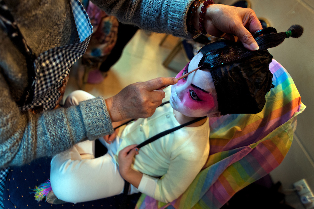 Yan-Ting, aged 4, from Cha Duk Chang - the Children's Cantonese Opera Association of Hong Kong -- has her wig fixed backstage. Unlike many performance groups now using synthetic wigs, real hair is used here in accordance with tradition. <br />
