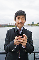 Portrait of confident businessman text messaging through cell phone outdoors