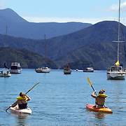 Kayakers on the water in Waikawa Bay on the Marlborough Sounds at the northern end of the South Island of New Zealand..Covering some 4,000 square kilometers of sounds, islands, and peninsulas, the Marlborough Sounds lie at the South Island's north-easternmost point, between Tasman Bay in the west and Cloudy Bay in the south-east. The main sounds, are Queen Charlotte Sound,  Pelorus Sound and Kenepuru Sound. Marlborough Sounds, New Zealand, 28th January 2011.  Photo Tim Clayton.