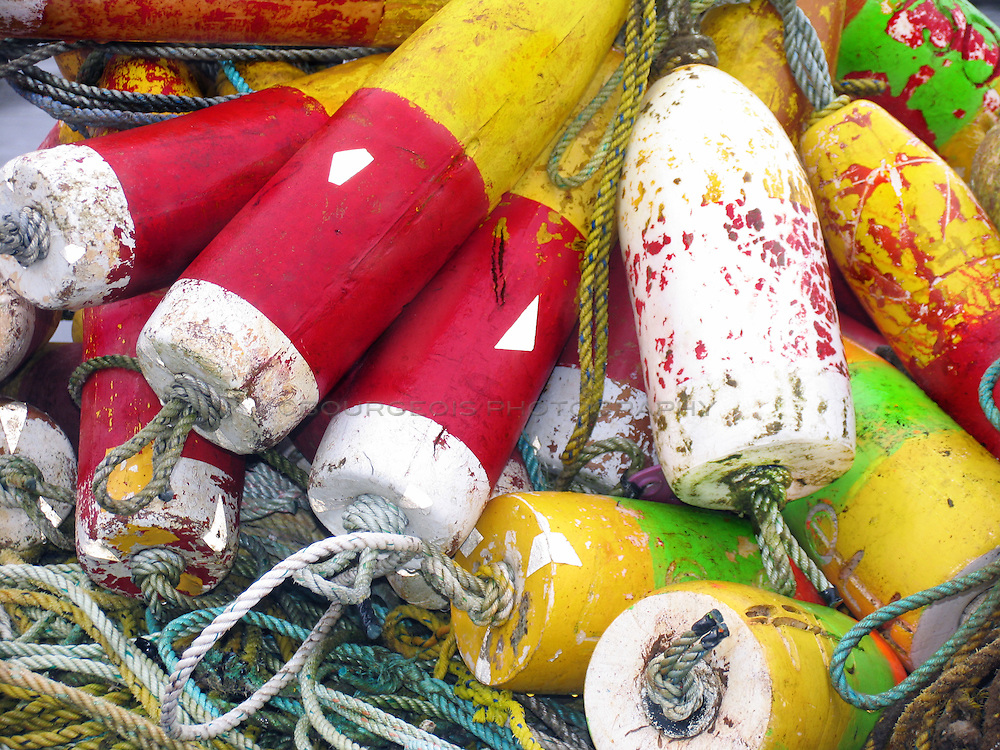 Buoys used in fishing off the Oregon Coast. Variety of colored buoys piled high with rope attached.