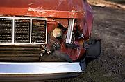 Close up of a broken headlight on a red truck